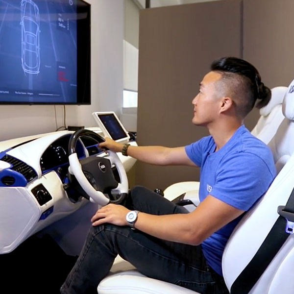 Young man sitting down in a demo car looking at screen.